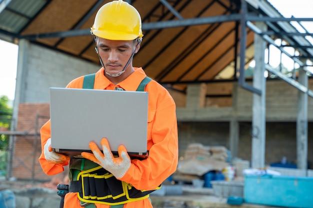 Elektrotechnici die veiligheidsharnas met laptop computer dragen die bij bouwwerf werken