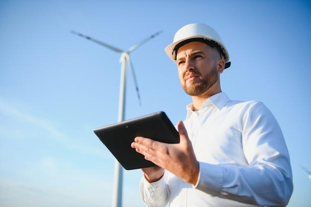 Elektrotechnici die werken bij een generatorstation voor windturbines met een laptopcomputer