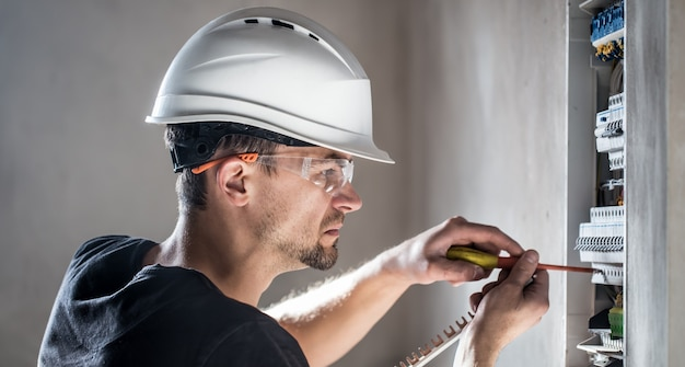 Elektrotechnicus die in een schakelbord met zekeringen werkt. installatie en aansluiting van elektrische apparatuur.