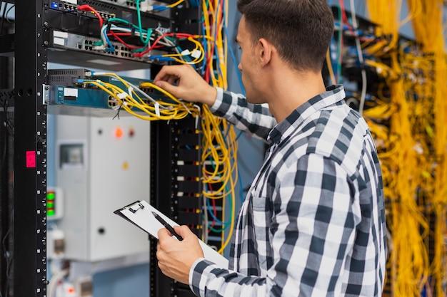 Elektrotechnisch ingenieur die aan netwerkschakelaar werkt