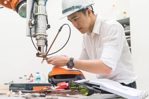 Elektrotechnisch ingenieur die met een robotmachine werkt