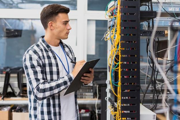 Elektrotechnisch ingenieur die op netwerkschakelaar kijkt