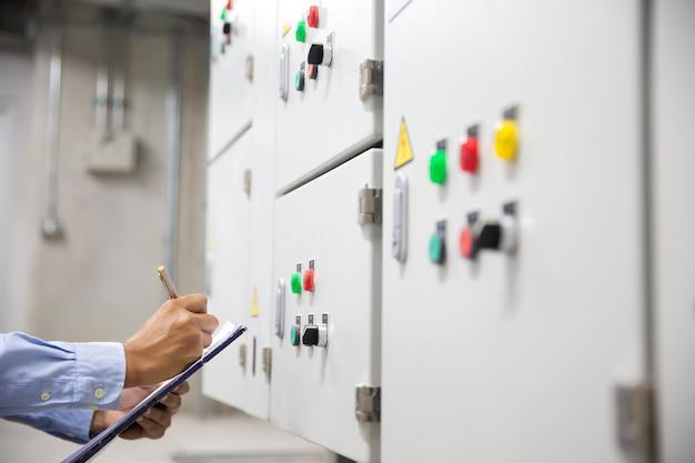 Elektrotechnisch ingenieur elektrische stroomspanning controleren op stroomonderbreker van luchtbehandelingsunit (ahu) startcontrolepaneel voor airconditioner.