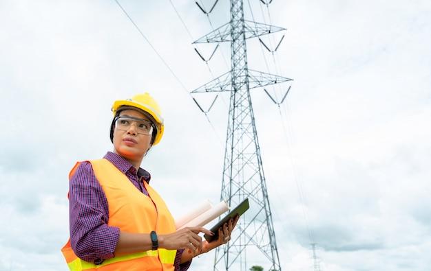 Elektrotechnisch ingenieur vrouwen die werken op de tablet. controle van de elektriciteitsnetten.