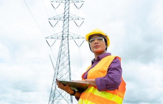 Elektrotechnisch ingenieur-vrouwen gebruiken laptop die werken en de elektriciteitsnetten controleren.