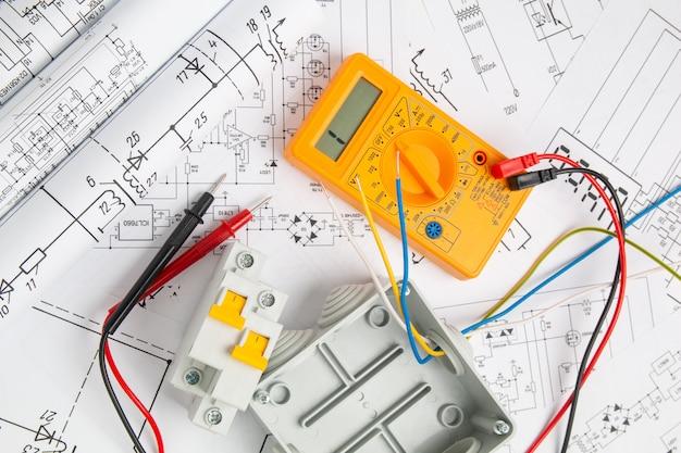 Elektrotekeningen, schakelaar, stroomonderbrekers, snijbox en digitale multimeter. installatie van voedingssystemen