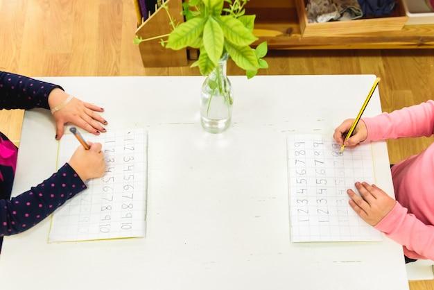 Elementaire studenten op een school die houtmaterialen van ander onderwijs gebruikt.