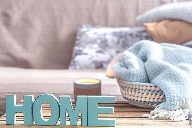 Elementen van gezellige huisinrichting op de tafel in de woonkamer met houten letters met het opschrift huis.