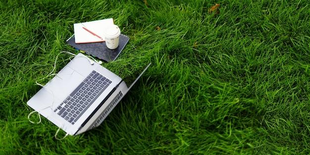 Elementen van werk of studie op het gras buiten een opengeklapte laptop een notitieboekje met een pen en een ecologische...