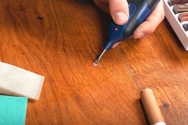 Eliminatie van defecten, spaanders, krassen in de laminaatvloer. restauratie van parket.