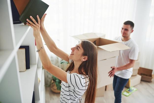 Elk boek moet op de juiste plaats staan. vrolijk jong stel in hun nieuwe appartement. conceptie van bewegen.