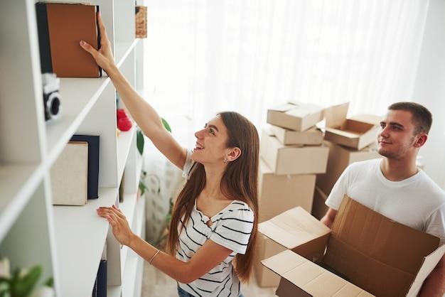 Elk boek moet op de juiste plaats zijn. vrolijk jong stel in hun nieuwe appartement. conceptie van verhuizen.