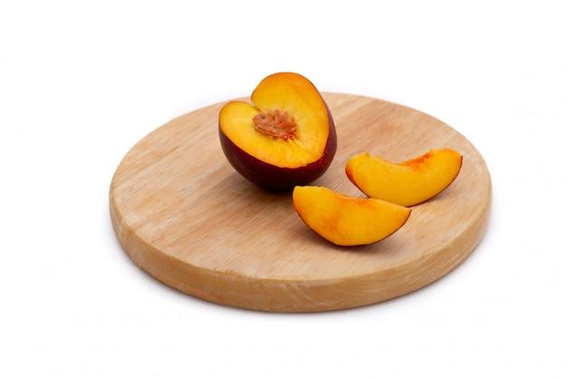 Elk of nectarine met gesneden stukken op houten plaat