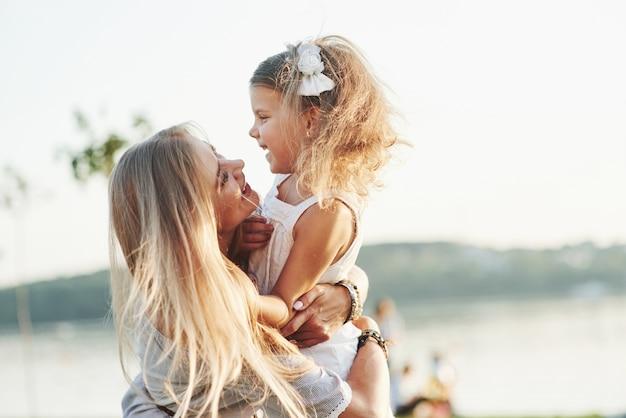 Elkaar aanstaren. portret van moeder en dochter die aan de buitenkant in het park glimlachen.