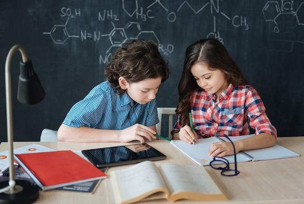 Elkaar helpen. bekwame, behulpzame, vriendelijke kinderen die op school zitten en genieten van de les terwijl ze aan het project werken en moderne gadgets gebruiken