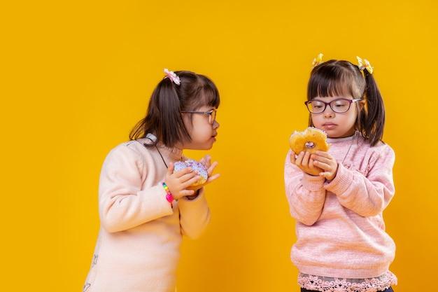 Elkaar voeden. geïnteresseerde kleine meisjes met het syndroom van down observeren hun donuts terwijl ze erop bijten