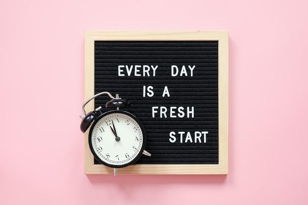 Elke dag is een nieuwe start. motiverende citaat op zwarte letter bord en zwarte wekker op roze achtergrond. concept inspirerende quote van de dag. wenskaart, briefkaart
