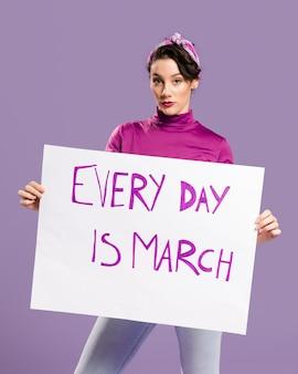 Elke dag is maart karton met vrouw die het bord vasthoudt