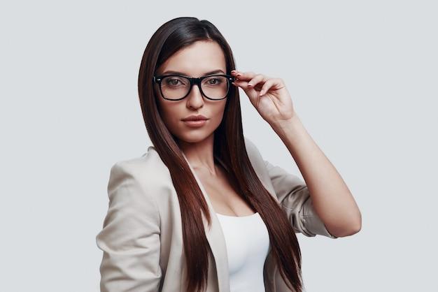 Elke dag nieuwe oplossing. aantrekkelijke jonge vrouw die naar de camera kijkt en een bril aanpast terwijl ze tegen een grijze achtergrond staat
