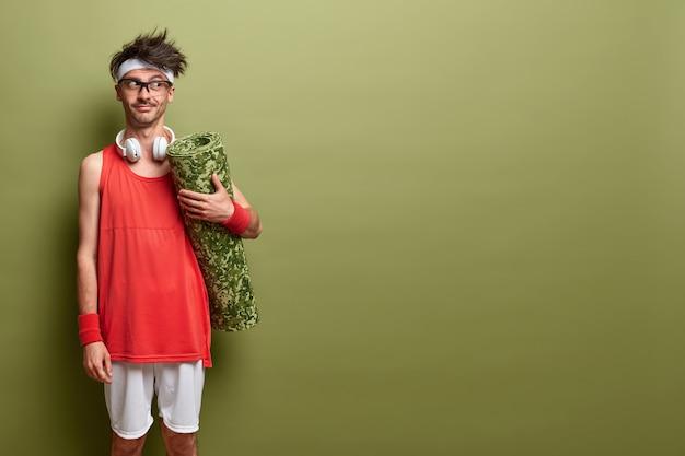 Elke dag sterker worden. nadenkende sportman komt in de sportschool om te oefenen, houdt opgerolde karemat vast, draagt actieve kleding en koptelefoon, staat tegen een groene muur, kopieert ruimte voor tekst.