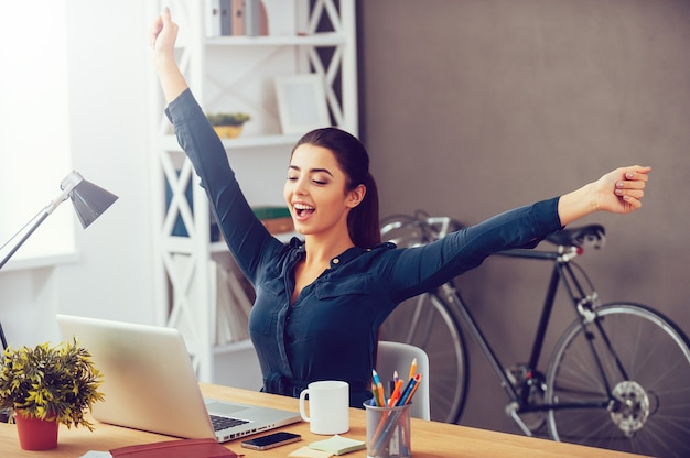 Elke dag winnen. aantrekkelijke jonge vrouw die haar handen uitstrekt en er opgewonden uitziet
