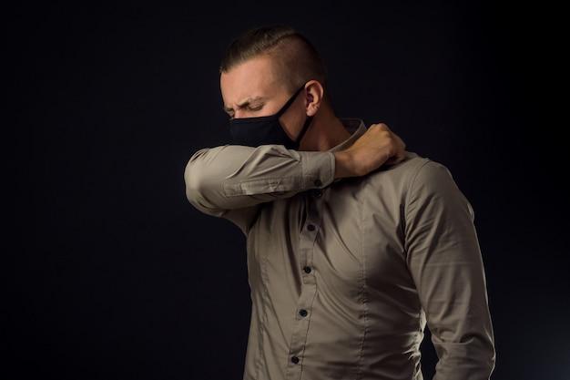 Elleboog hoest. man in beschermend masker over zwarte muur