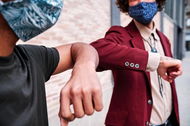 Elleboog stoten. ellebooggroet om de verspreiding van het coronavirus (covid-19) te voorkomen. mannen in overhemden ontmoeten elkaar op straat met blote handen. in plaats van te begroeten met een handdruk of een knuffel, stoten ze tegen de ellebogen