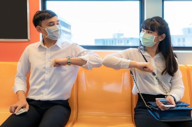 Elleboogbult is een nieuwe nieuwe begroeting om de verspreiding van coronavirus te voorkomen. twee aziatische zakenvrienden ontmoeten elkaar in de metro.