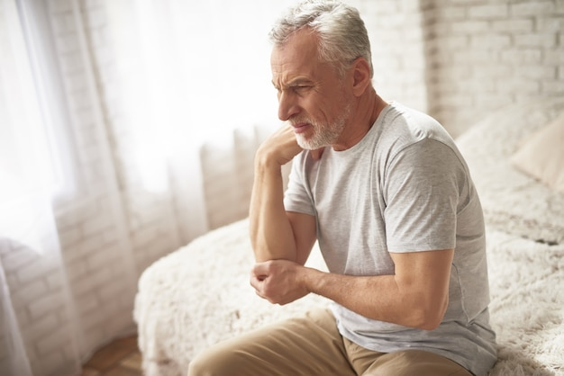 Elleboogpijn in ochtend oude man die aan artritis lijdt.