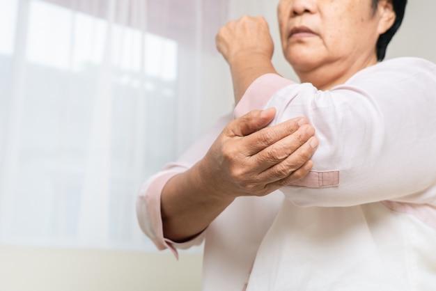 Elleboogpijn oude vrouw die thuis aan elleboogpijn lijdt, gezondheidszorgprobleem van hoger concept