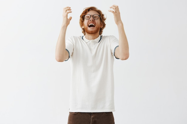 Ellendig en boos bebaarde roodharige man poseren tegen de witte muur met bril
