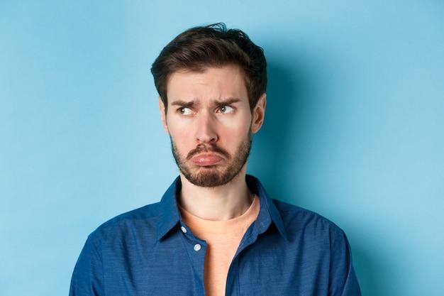 Ellendige en teleurgestelde man die kinderachtig handelt, mokkend en naar links kijkt naar lege ruimte met beledigd gezicht, staande op een blauwe achtergrond.