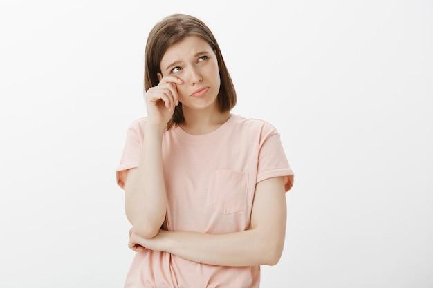 Ellendige, onzekere vrouw die haar traan afveegt en er beledigd uitziet, zich verdrietig of eenzaam voelt