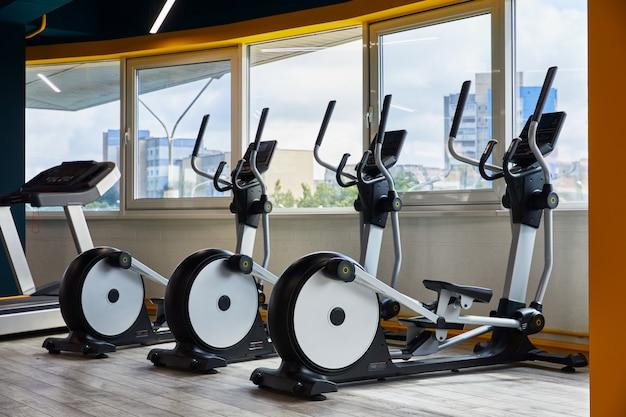 Elliptische trainers staan in de rij, gym met ramen, uitzicht over de hele stad