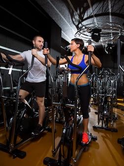 Elliptische walker trainer man en vrouw op zwarte sportschool