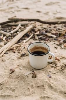 Emaille mok met warme drank staande in een zand op een wild strand, selectieve aandacht