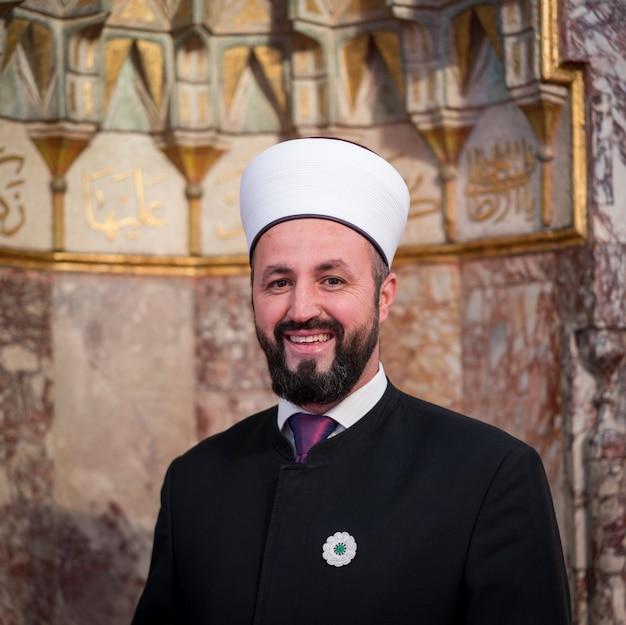 Emam in moskee met verzen uit kuran aan de muur