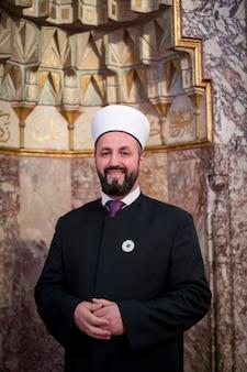 Emam in moskee met verzen van kuran op de muur