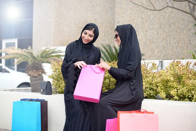 Emarati arabische vrouwen die uit winkelen komen