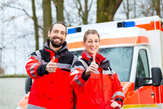 Emergency arts en verpleegkundige staan voor ambulance