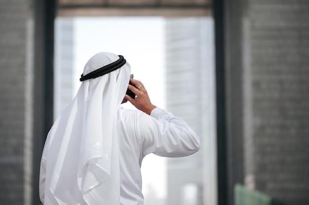 Emirati die traditionele kandura draagt die met slimme telefoon spreekt.