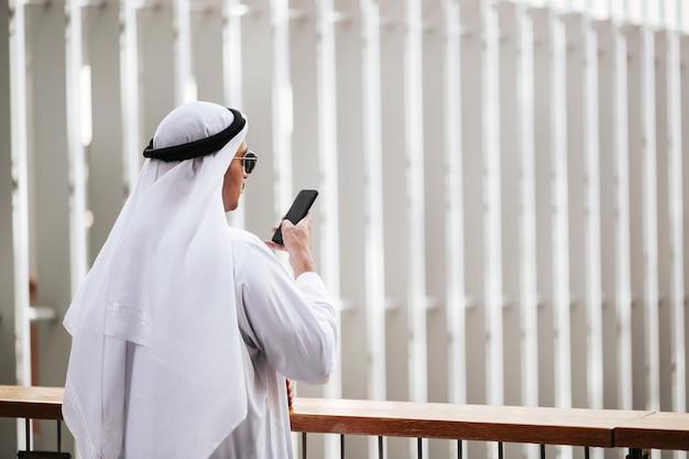Emirati man traditionele kandura dragen in stedelijke stad emiraten levensstijl praten met slimme telefoon.