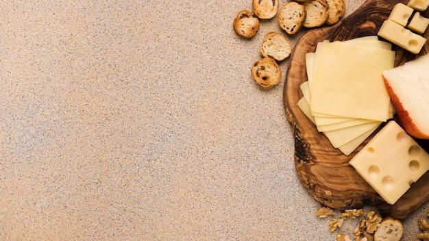 Emmentaler en gouda kaas met plakjes op coaster met sneetjes brood en walnoot over beige gestructureerde achtergrond