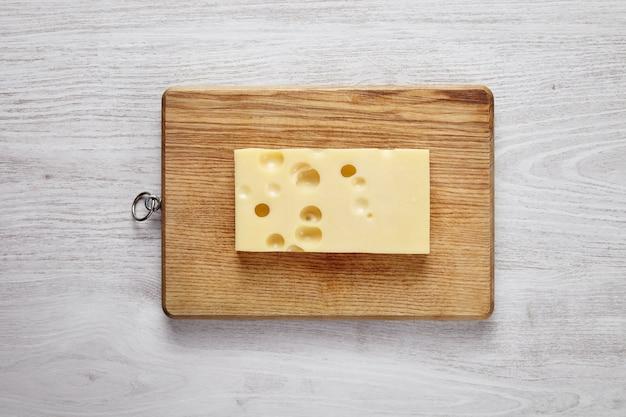 Emmentaler kaas geïsoleerd aan boord op wit geborsteld boerderijtafel