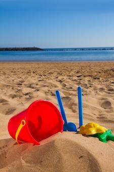 Emmer met plastic strandspeelgoed in zand aan de kust op zonnige zomerdag