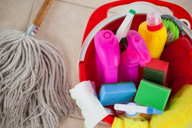 Emmer met schoonmaakproducten en dweil op tegelvloer