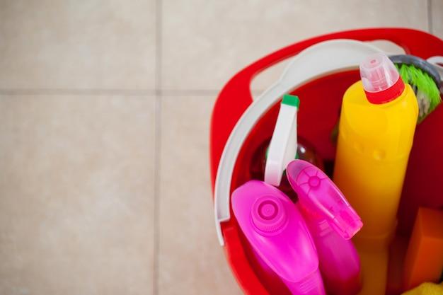Emmer met schoonmaakproducten op tegelvloer