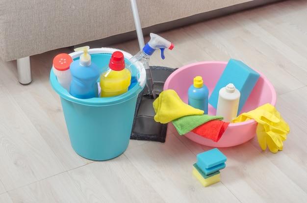 Emmer met verschillende schoonmaakproducten met servetten, sponzen en handschoenen op de vloer.