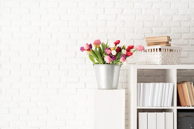 Emmer met verse tulp bloemen naast de boekenkast op witte bakstenen muur achtergrond