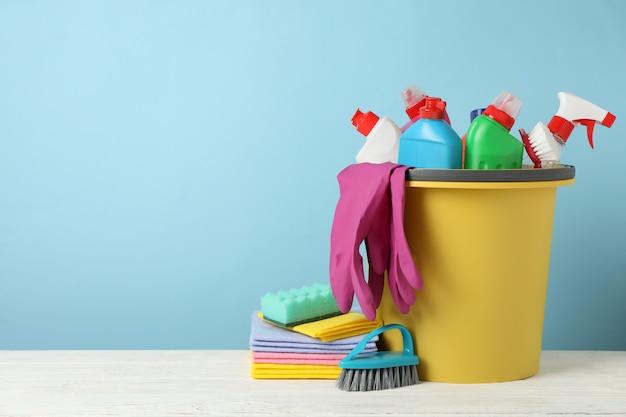 Emmer met wasmiddel en schoonmaakproducten op blauwe achtergrond, ruimte voor tekst